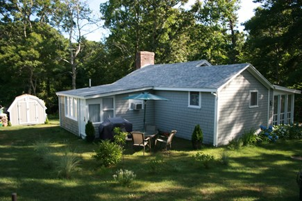 East Orleans Cape Cod vacation rental - The side yard boasts a table, chairs, and gas grill.