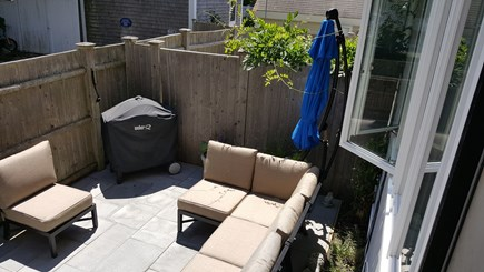 Provincetown Cape Cod vacation rental - View of the patio seating, grill and umbrella from entry steps.