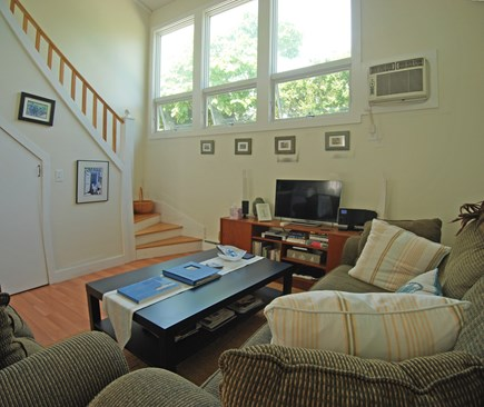 Provincetown Cape Cod vacation rental - Living area with vaulted ceiling, tall windows, and stair to loft