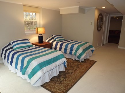 South Chatham Cape Cod vacation rental - Lower living area with two twin beds with full size door/windows.