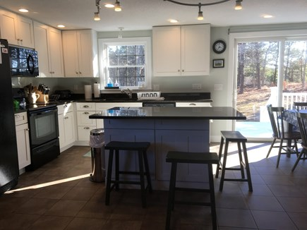 Eastham Cape Cod vacation rental - Bright sunny kitchen with sliding door out to deck .