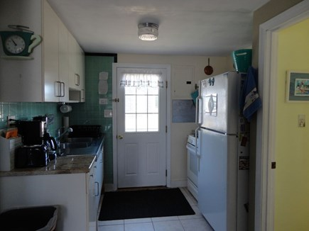 West Dennis Cape Cod vacation rental - Kitchen with door to back yard and more outdoor seating