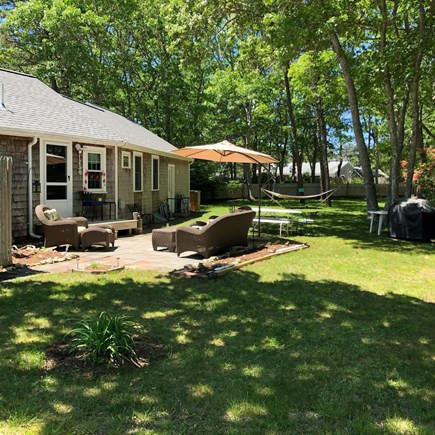 West Dennis Cape Cod vacation rental - Relaxin backyard with hammock, patio, grill and room for games