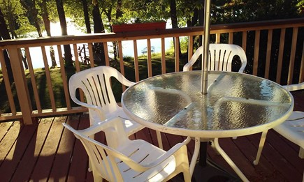 East Falmouth on fresh pond Cape Cod vacation rental - Table with umbrella and chairs on our over-sized deck above lake