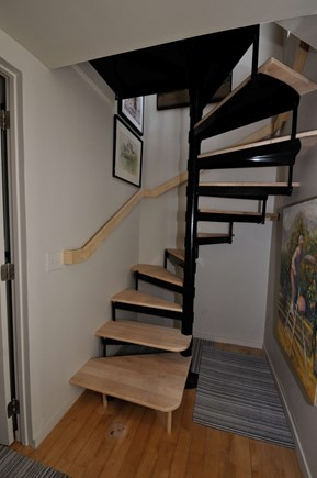 Provincetown Cape Cod vacation rental - Wooden spiral staircase to second floor living room and kitchen.