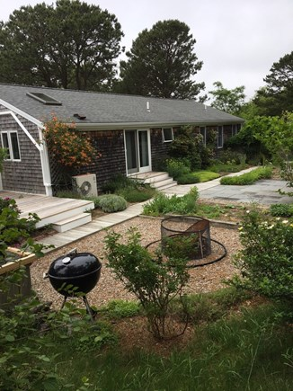 North Eastham Cape Cod vacation rental - House back with fire pit, grill, and garden