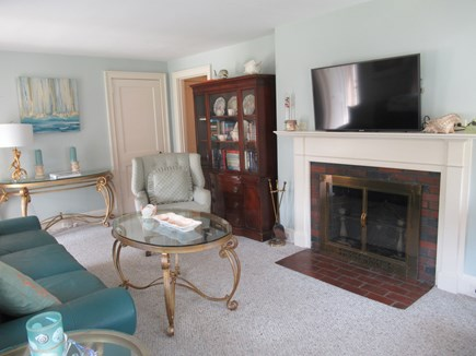 Hyannis Cape Cod vacation rental - New Flat Screen TV over fireplace, comfy chair and book case