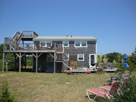 Truro Cape Cod vacation rental - Level spacious rear yard with two chaise lounges and more chairs.