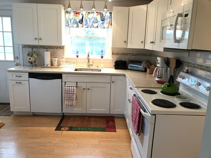 Truro Cape Cod vacation rental - Sunny kitchen faces backyard plus 4 stools and table (not shown).
