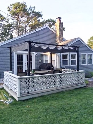Dennis Port Cape Cod vacation rental - Side view of the house with deck, table for 8 and sunshade.