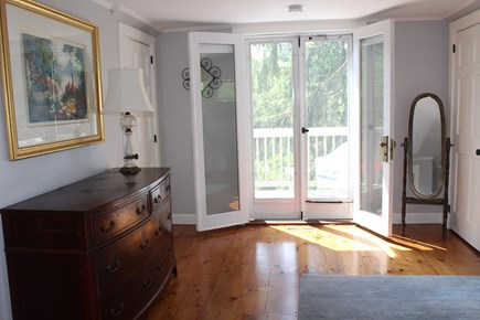 In The Heart of Brewster Cape Cod vacation rental - Master Bedroom view to balcony.  TV in the room.