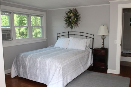 In The Heart of Brewster Cape Cod vacation rental - The master bedroom with queen bed, dressing room and balcony.