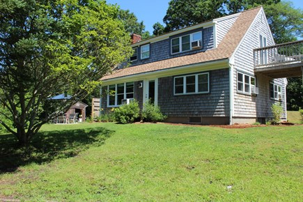 In The Heart of Brewster Cape Cod vacation rental - The front of the home featuring the yard & master bedroom deck.