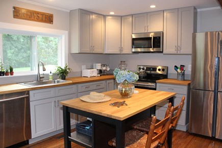 In The Heart of Brewster Cape Cod vacation rental - Kitchen with stainless appliances and island.