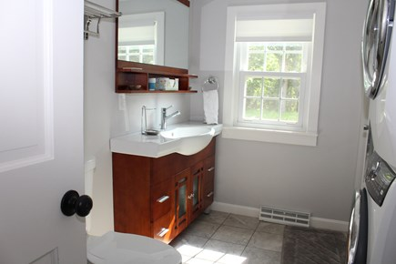 In The Heart of Brewster Cape Cod vacation rental - First floor bath with an oversized shower and washer and dryer.