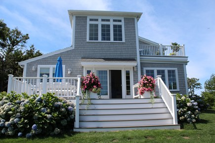 North Chatham Cape Cod vacation rental - Side entrance. Multiple decks with water views and flowers.