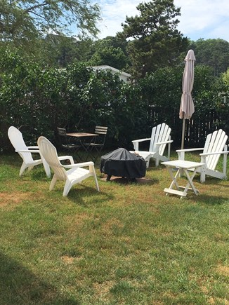 Wellfleet Cape Cod vacation rental - Private backyard with fencing, fire pit and lilac bushes.