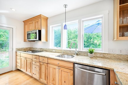 Truro Cape Cod vacation rental - Kitchen that opens to dining area and also exits to yard.