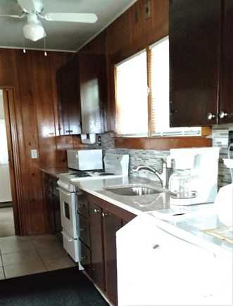 Truro Cape Cod vacation rental - Galley kitchen with appliances needed for cooking, washer, fan.