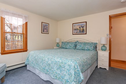 Eastham Cape Cod vacation rental - First-floor bedroom with king-size bed and sitting chair.