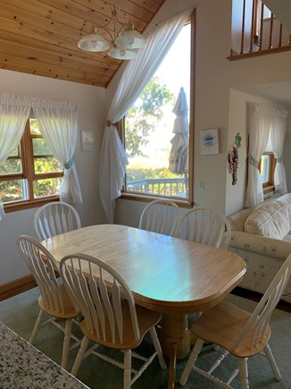 Eastham Cape Cod vacation rental - Dining area next to kitchen and living area with open ceiling.