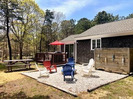 Eastham Cape Cod vacation rental - Back yard deck and firepit seating area with cornhole, horseshoes