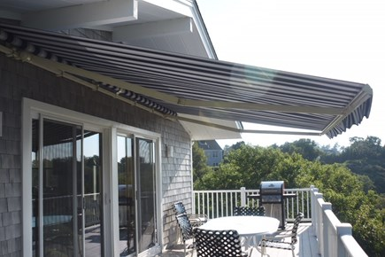 Dennis Cape Cod vacation rental - Deck area with dining table, awning and gas grill