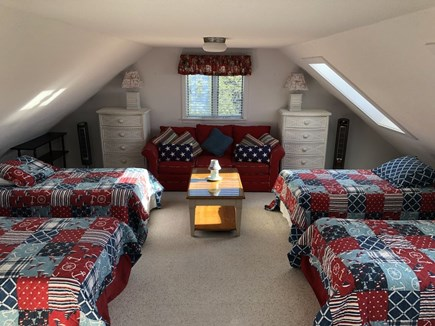 Eastham Cape Cod vacation rental - Cozy sky-lit loft with four full beds, sofa, chairs and TV / DVD.