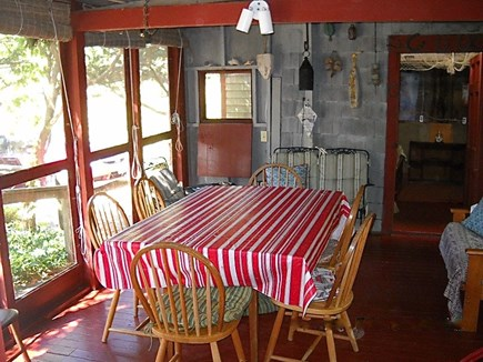 Wellfleet, Pine Point Cape Cod vacation rental - Dining table on screen porch.  Summer bedroom beyond.
