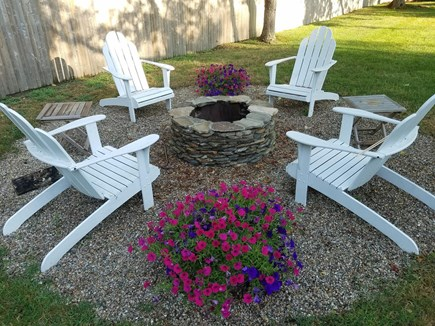 North Eastham Cape Cod vacation rental - Adirondack chairs and fire pit in the backyard.