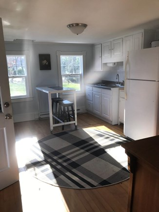 North Eastham Cape Cod vacation rental - Kitchen with full-sized fridge and breakfast bar with two stools.