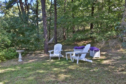 Truro Cape Cod vacation rental - Adirondack chairs and table for outdoor lounging, hammock beyond