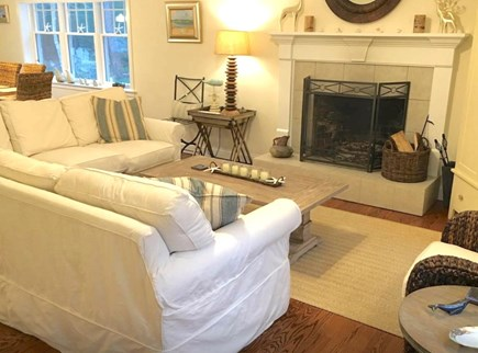 Mashpee Cape Cod vacation rental - Living room off of dining area and kitchen with wood-burning FP