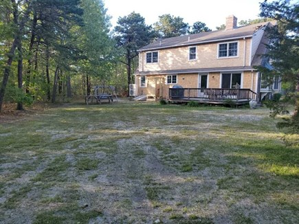 Eastham Cape Cod vacation rental - Deck with table, chairs and BBQ overlooking sizable yard.