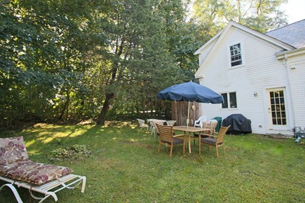 Dennis Cape Cod vacation rental - Side yard with sitting areas & door to kitchen for easy grilling
