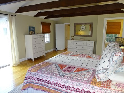 East Dennis Cape Cod vacation rental - Master bedroom showing slider to deck, bath, multiple dressers