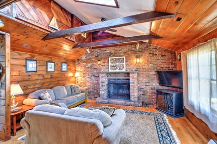 Sandwich Cape Cod vacation rental - Living Room with wood floors, cathedral ceiling and fireplace.
