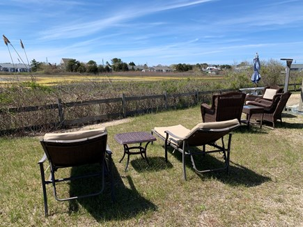 West Dennis Cape Cod vacation rental - Backyard with outdoor seating & lounge chairs overlooking marsh