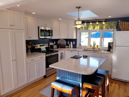 Dennis, Miramar Beach House Cape Cod vacation rental - Kitchen with island and stools open to LR and breezeway