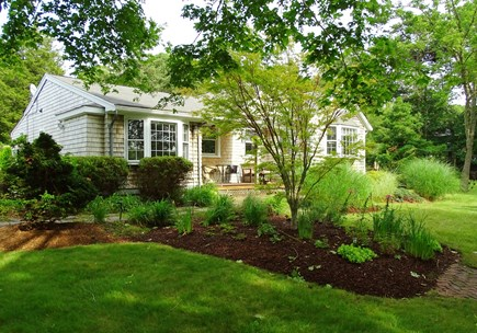 East Falmouth Waterfront Cape Cod vacation rental - Side view of house with lawn and gardens