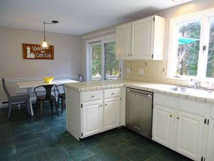 Eastham Cape Cod vacation rental - Kitchen area with seating nook and slider to deck