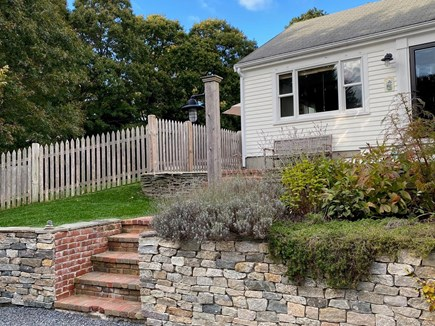 East Orleans Cape Cod vacation rental - Sunny side entrance from driveway with stone patio and bench.