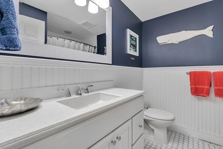 Dennis Cape Cod vacation rental - Main floor bathroom - single vanity with tub and shower curtain.