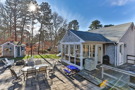 Dennis Cape Cod vacation rental - Backyard with grill, dining table, and fire pit.