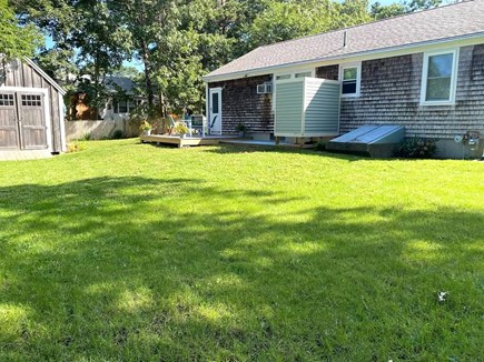 West Yarmouth Cape Cod vacation rental - Manicured backyard lawn with view of shed, deck and shower.