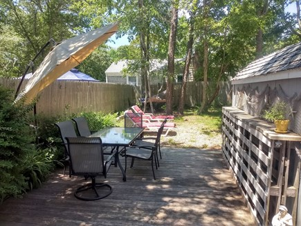 Yarmouth Cape Cod vacation rental - Back yard with deck, gas grill, chaise lounges, and hammock.