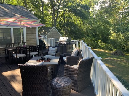 Orleans Cape Cod vacation rental - Summer photo of deck - fire table, dining w/ umbrella, gas grill