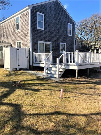 Dennis Port Cape Cod vacation rental - Back yard with deck and furniture and grill