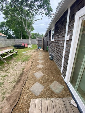 West Dennis Cape Cod vacation rental - Backyard and walkway to outdoor shower. Fire pit area off to left