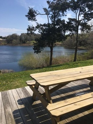 East Orleans Cape Cod vacation rental - Front deck with picnic table. Property slopes to pond's edge.